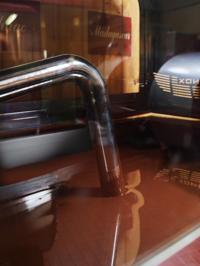 Opération de conchage dans un bac en inox rempli de chocolat fondu brun clair. On voit le tube métallique qui brasse cette pâte fluide.